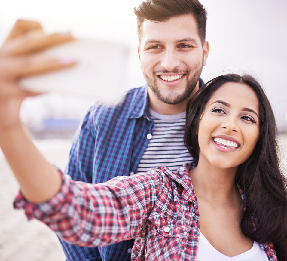 couple taking selfie outside smiling teeth